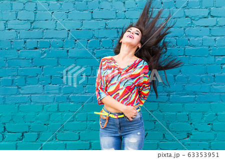 Summer and joy concept - Joyful young woman flicking her hair outdoors, smiling and feeling joyful and free and having fun, copy space